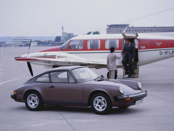 1977 Porsche 911 Carrera parked in front of a plane
